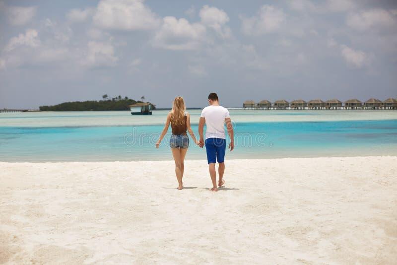 Hintere Ansicht des Paarhändchenhaltens und -c$gehens zur blauen Ozeanlagune auf Malediven am Luxuskurort Reise und lizenzfreie stockfotos