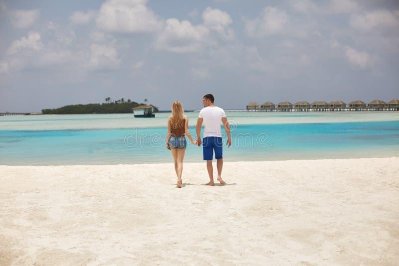 Hintere Ansicht des Paarhändchenhaltens und -c$gehens zur blauen Ozeanlagune auf Malediven am Luxuskurort Reise und lizenzfreies stockbild
