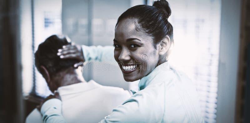 Hintere Ansicht des Porträts des lächelnden weiblichen Therapeuten, der dem älteren männlichen Patienten den Hals massiert gibt lizenzfreies stockbild