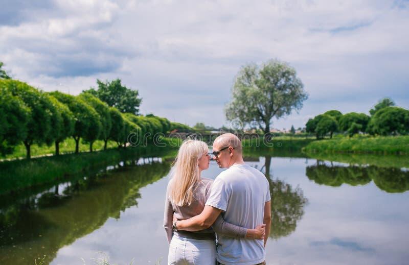 Hintere Ansicht des reizenden Paarmannes und -frau, die nahe dem umarmenden und entspannenden Fluss oder See sitzt stockfotos