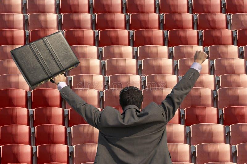 Hintere Ansicht des siegreichen Geschäftsmannes mit dem Aktenkoffer, der Reihen von roten Sitzen am Stadion gegenüberstellt lizenzfreie stockfotos