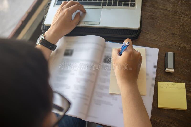 Hintere Ansicht des Studenten klebrige Anmerkung auf Arbeitsbuch schreibend lizenzfreie stockfotografie
