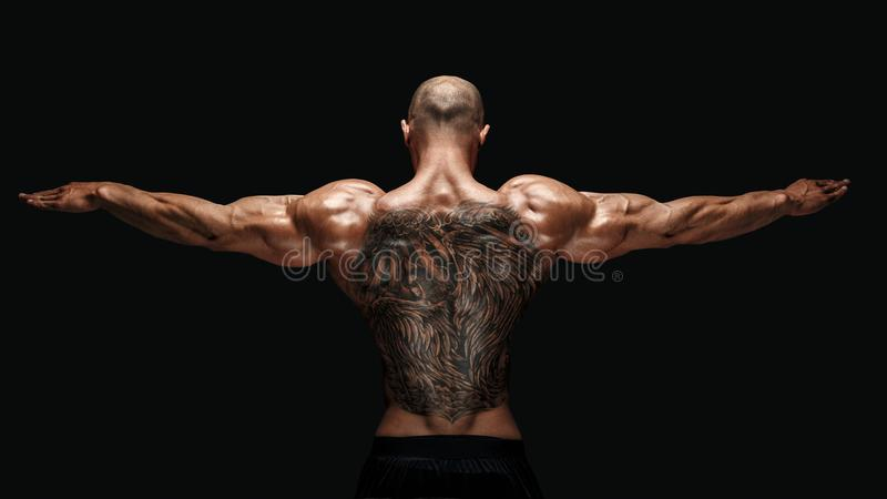 Hintere Ansicht des tattoed Bodybuilders mit den ausgestreckten Armen lizenzfreies stockfoto