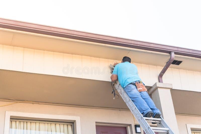 Hintere Ansicht des Technikers Überwachungskamera auf Dach installierend lizenzfreies stockfoto