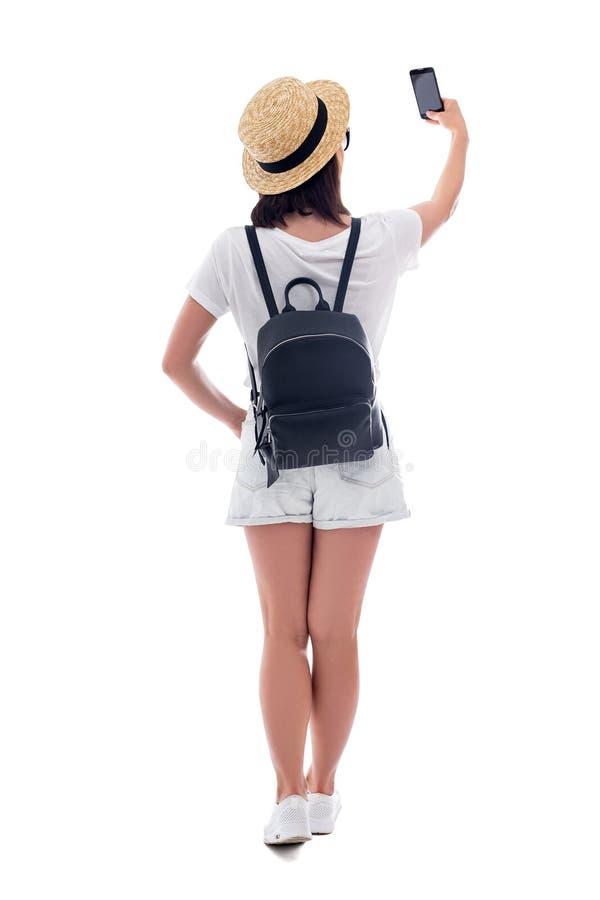 Hintere Ansicht des Touristen der jungen Frau im Strohhut, der selfie Foto mit dem Smartphone lokalisiert auf Weiß macht lizenzfreie stockfotografie
