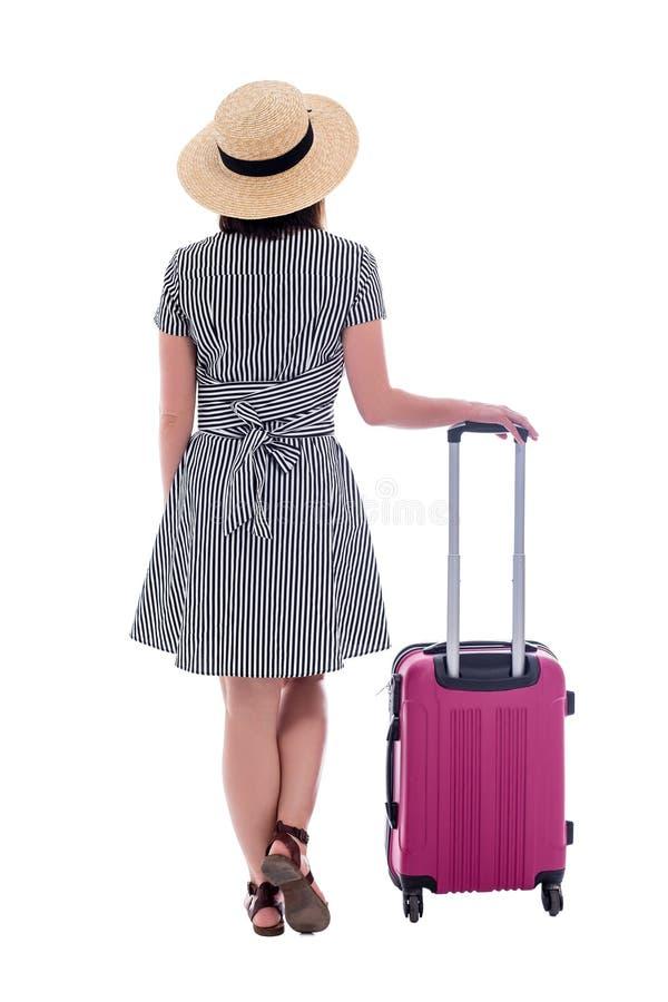 Hintere Ansicht des Touristen der jungen Frau im Strohhut und im Sommerkleid mit dem rosa Koffer lokalisiert auf Weiß stockfotos