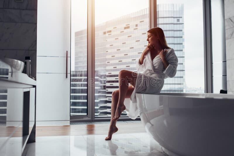 Hintere Ansicht des tragenden weißen Bademantels der jungen Frau, der im Badezimmer heraus schaut das Fenster mit Badewanne im Vo stockbilder