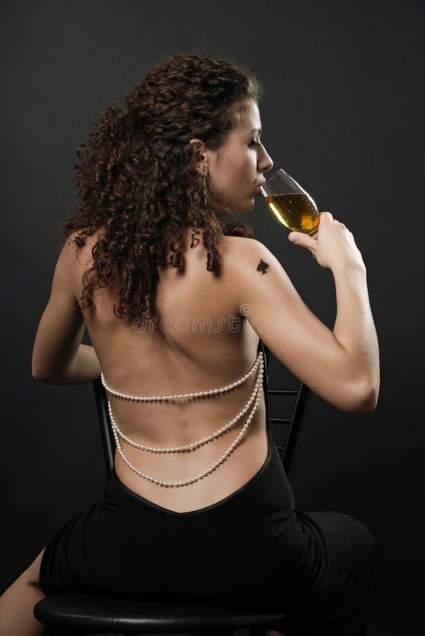 Hintere Ansicht des trinkenden Weins des reizvollen Mädchens stockfotos