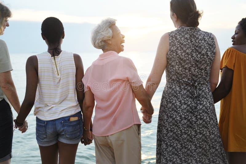 Hintere Ansicht des verschiedenen älteren Frauenhändchenhaltens zusammen an lizenzfreie stockfotos