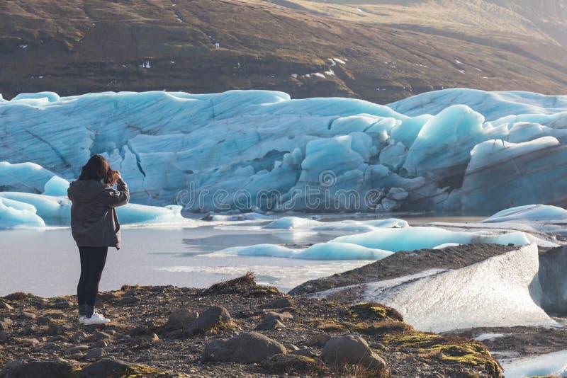 Hintere Ansicht des weiblichen Touristenphotographen, der Foto der schönen Glättungslandschaft von Skaftafell-Gletscher Vatnajoku stockfoto