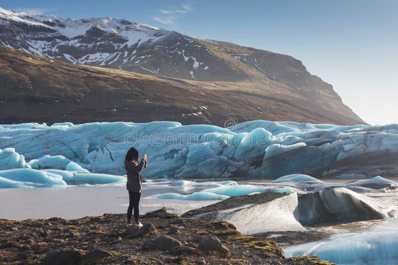 Hintere Ansicht des weiblichen Touristenphotographen, der Foto der schönen Glättungslandschaft von Skaftafell-Gletscher Vatnajoku stockfotos
