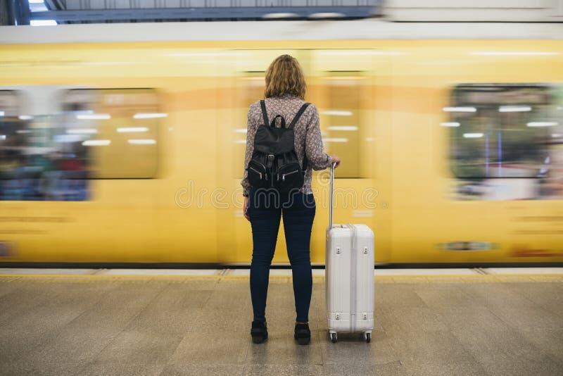 Hintere Ansicht einer blonden Frau, die an der Zugplattform wartet stockfotografie
