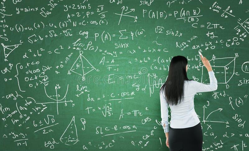 Hintere Ansicht einer durchdachten Frau, die Matheberechnungen auf grünes Kreidebrett schreibt lizenzfreie stockfotografie