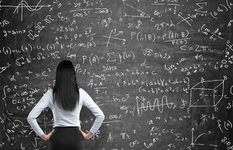 Hintere Ansicht einer durchdachten Frau, die versucht, mathematische Probleme zu lösen stockfotografie