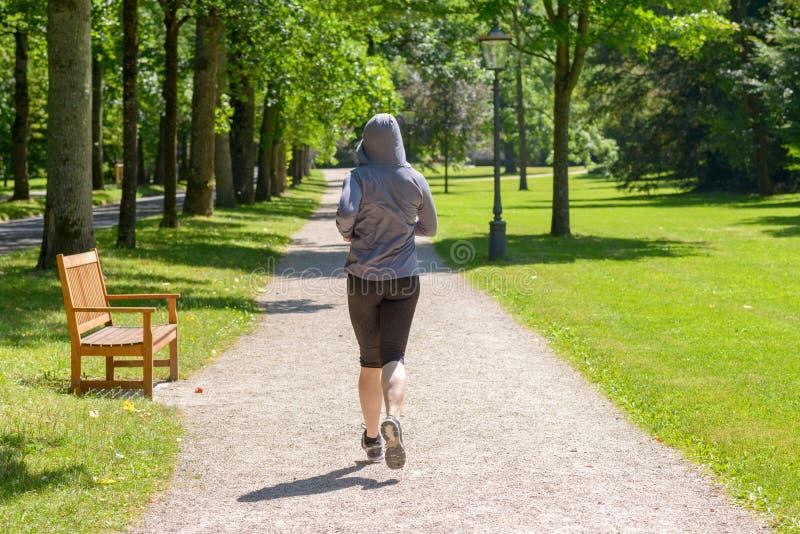 Hintere Ansicht einer Frau, die in einen Park läuft stockfoto