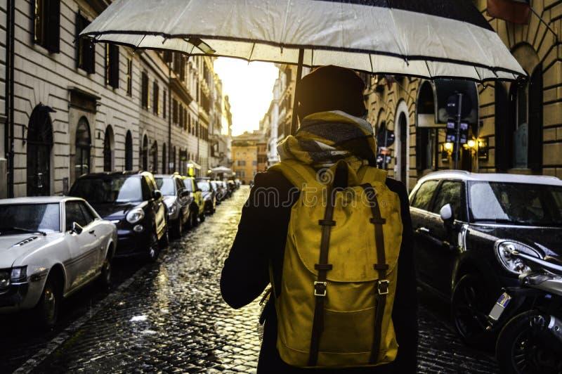 Hintere Ansicht einer Frau, die einen Regenschirm unter dem Regen hält und hinunter die Straße in Rom, Italien geht stockbild