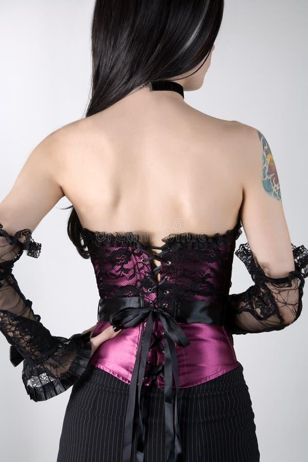 Hintere Ansicht einer Frau im purpurroten Korsett mit Spitzeüberlagerung stockfotografie