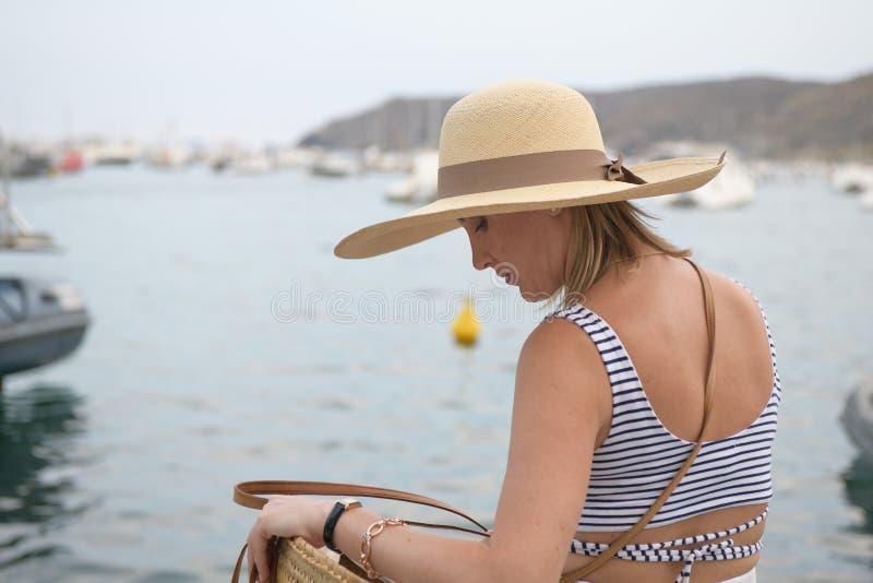Hintere Ansicht einer Frau mit einem Hut, der nach etwas in ihrer Tasche über Küstenpromenade sucht stockfotos