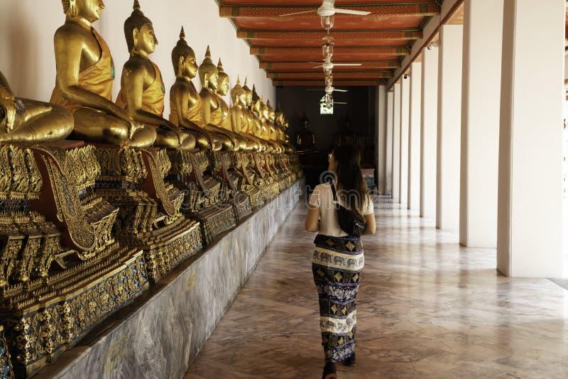 Hintere Ansicht einer gehenden Seite der Frau zu ausgerichteten goldenen Buddha-Statuen am Smaragdtempel in Bangkok stockfotografie