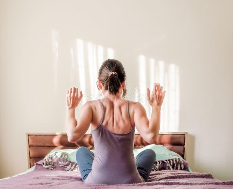 Hintere Ansicht einer kaukasischen Frau, die im Bett aufwacht und ihre Arme mit Kopienraum ausdehnt lizenzfreie stockfotos