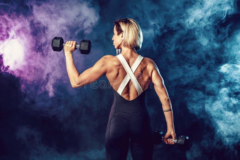Hintere Ansicht einer sportlichen Frau in der modernen Sportkleidung tut die ?bungen mit Dummk?pfen Foto der muskul?sen Frau auf  lizenzfreie stockfotografie
