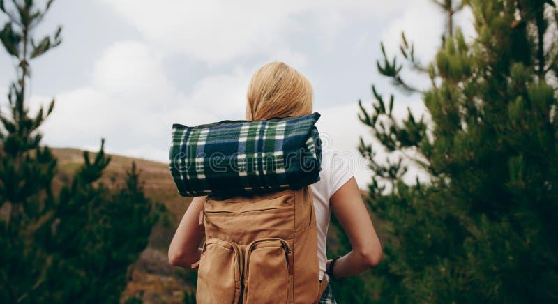 Hintere Ansicht einer tragenden reisenden Ausrüstung der Forscherfrau stockfoto