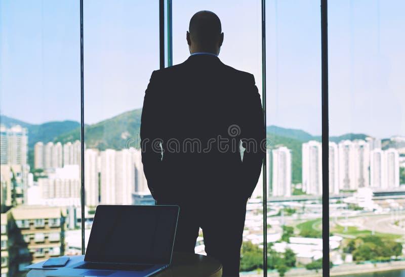 Hintere Ansicht eines überzeugten Unternehmers des Mannes schaut im Großen Bürofenster stockbild