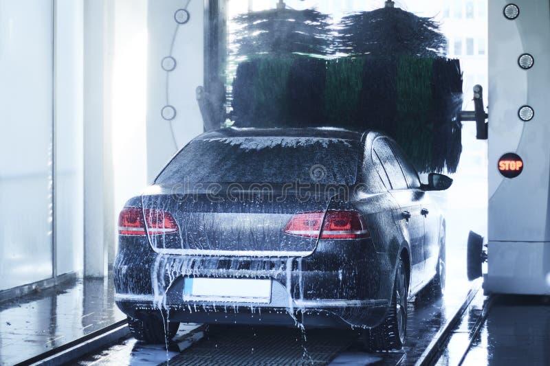 Hintere Ansicht eines Autowäschen, das ein Auto mit drehenden Bürsten säubert lizenzfreies stockfoto