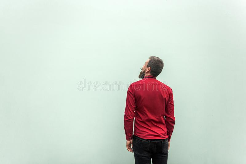 Hintere Ansicht eines Erfolgsgeschäftsmannes, auf grauem Hintergrund Oben schauen und Träumen stockfotografie