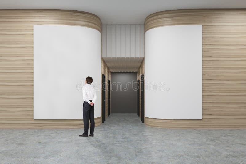 Hintere Ansicht eines Geschäftsmannes in einem weißen Hemd, das ein Plakat in einem Büroflur mit gerundeten hölzernen Wänden betr stock abbildung