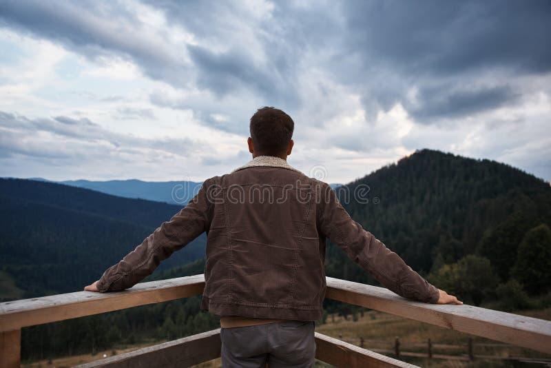 Hintere Ansicht eines Mannes, der auf dem Balkon steht stockfotos