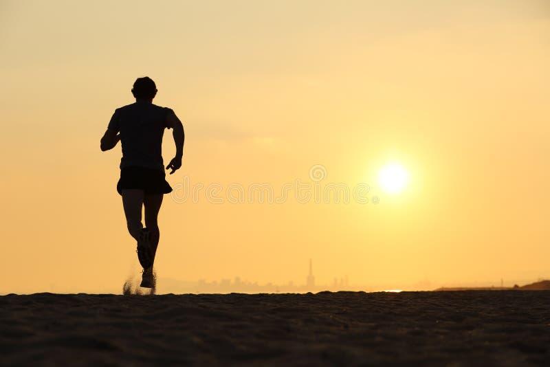 Hintere Ansicht eines Mannes, der auf dem Strand bei Sonnenuntergang läuft lizenzfreie stockfotografie