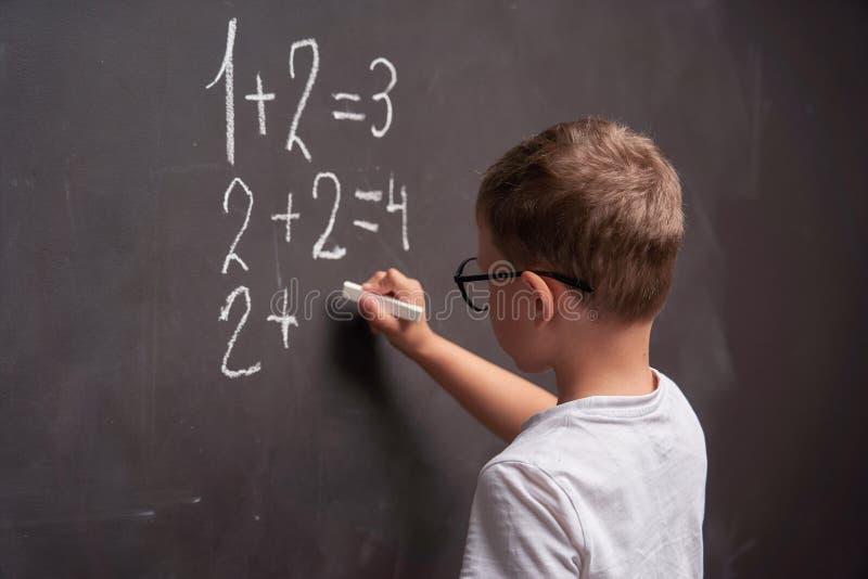 Hintere Ansicht eines Schülers löst ein mathematisches Beispiel auf einer Tafel in einer Matheklasse stockfoto