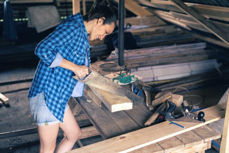 Hintere Ansicht eines weiblichen Tischler Sawing mit einer Metallsäge verschalt, Holzbearbeitung zu Hause lizenzfreie stockfotografie