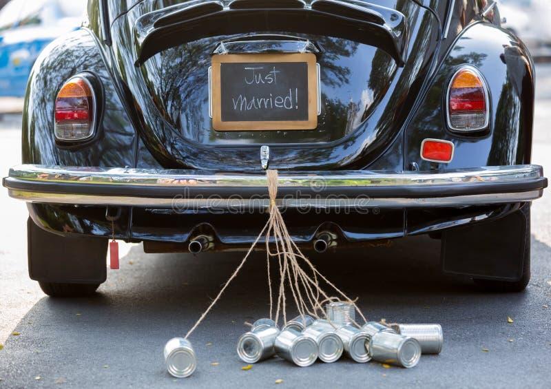Hintere Ansicht eines Weinleseautos mit gerade verheiratetem Zeichen und Dosen attac stockfotos
