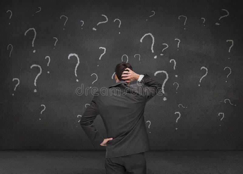 Hintere Ansicht eines zweifelhaften Geschäftsmannes, der verschiedene Frage betrachtet lizenzfreie stockbilder