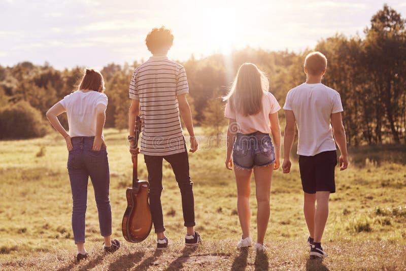 Hintere Ansicht freundlichen Mitschüler recreat draußen bei sonnigem Wetter, haben Weg über Wiese, Gebrauchsgitarre für Gesanglie lizenzfreies stockfoto