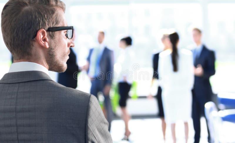 Hintere Ansicht Geschäftsmann, der nahe dem Bürofenster steht lizenzfreie stockfotografie