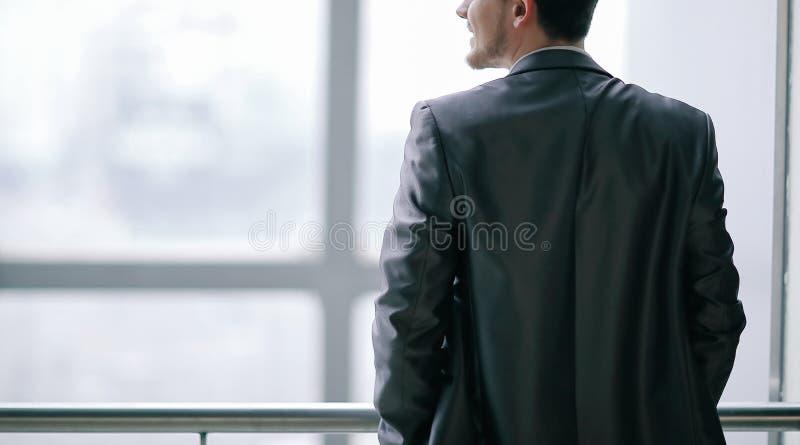 Hintere Ansicht Gesch?ftsmann in der Freizeitkleidung, die nahe dem B?rofenster steht und denkt lizenzfreie stockbilder