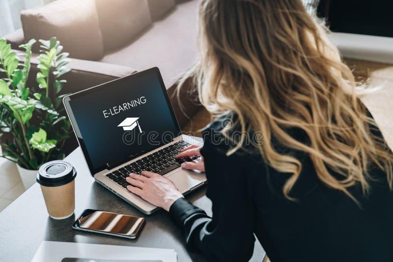 Hintere Ansicht Junge Frau arbeitet an Laptop mit Aufschrift auf Schirme-learning und Bild der quadratischen akademischen Kappe lizenzfreie stockfotografie