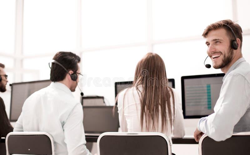 Hintere Ansicht junges Kundendienstvertreter, das an seinem Schreibtisch sitzt lizenzfreie stockfotos