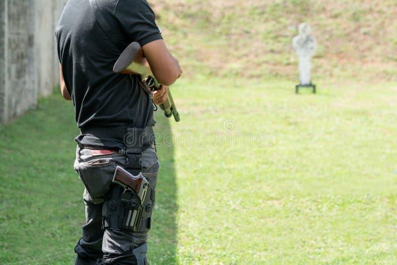 Hintere Ansicht Mannholdingschrotflinte und Pistole auf dem Kalb an der Front des Ziels im Schießstand tragen Mann-übendes Feuer- lizenzfreie stockbilder