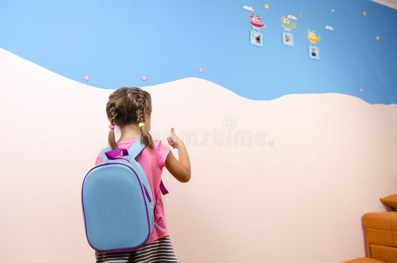 Hintere Ansicht, nettes kleines Mädchen mit Zöpfen und Rucksack stockfotografie