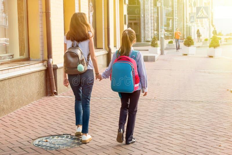 Hintere Ansicht, Studentinnen gehen zum Schulhändchenhalten stockfotos