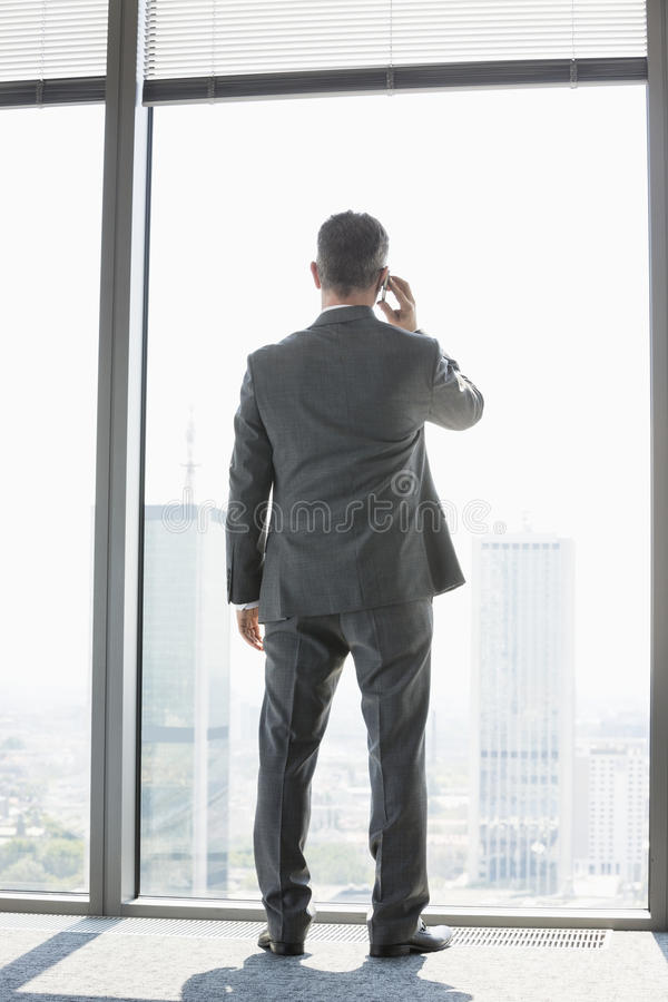 Hintere Ansicht in voller Länge des reifen Geschäftsmannes unter Verwendung des Handyweiß, das nahes Fenster steht stockbild