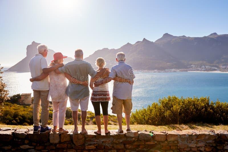 Hintere Ansicht von den älteren Freunden, die touristischen Markstein auf den Gruppen-Ferien stehen auf Wand besuchen lizenzfreie stockbilder