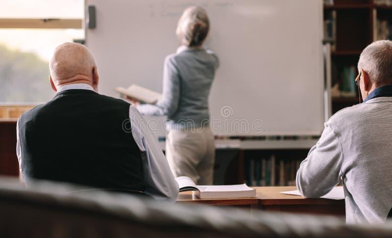 Hintere Ansicht von den älteren Männern, die in einem Klassenzimmer sitzen lizenzfreies stockfoto