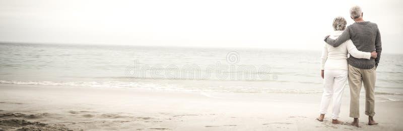 Hintere Ansicht von den älteren Paaren, die am Strand umfassen lizenzfreie stockfotografie
