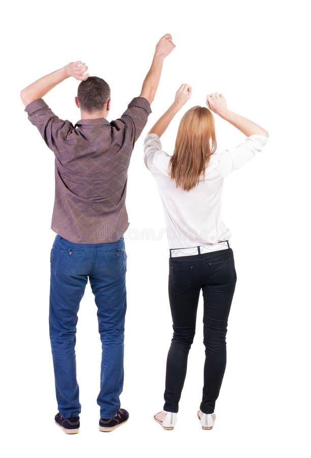 Hintere Ansicht von den frohen Paaren, die oben Sieghände feiern stockbilder