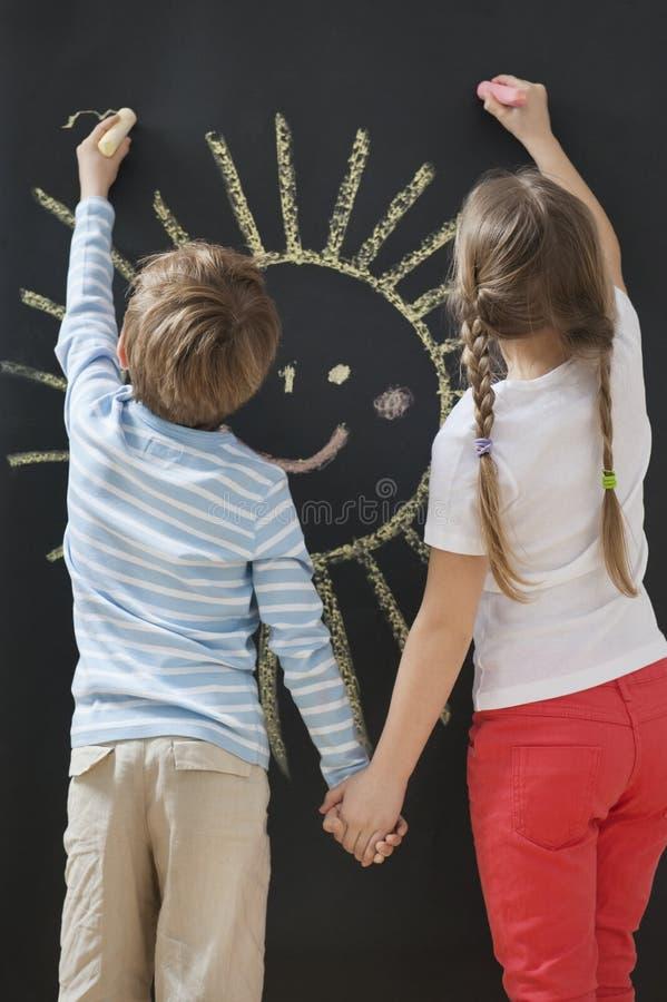 Hintere Ansicht von den Geschwister, die Sonne auf Tafel während Händchenhalten zeichnen stockbild